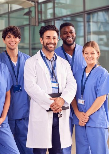 portrait-of-smiling-medical-team-standing-in-moder-narrow